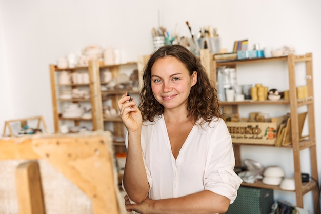 Portret van een mooie artistieke vrouw die een krijtje vasthoudt terwijl ze een foto op canvas tekent in een workshop of masterclass