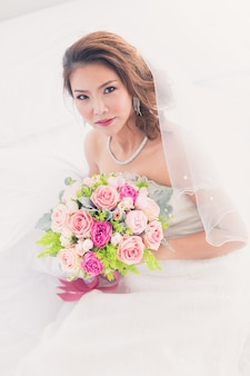 Portret van een mooie aziatische bruid die in de kleedkamer zit en een boeket bloemen vasthoudt met een witte achtergrond.