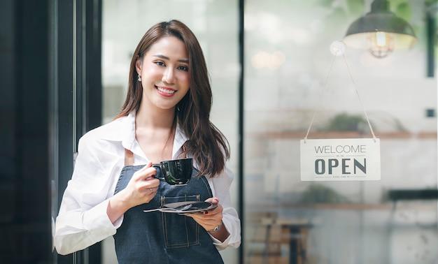 Portret van een mooie aziatische ondernemer die een beker vasthoudt die bij de deuropening van haar winkel staat met een open bord.