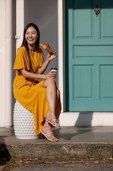 Portret van een mooie aziatische vrouw die buiten in de stad poseert terwijl ze koffie en een croissant drinkt