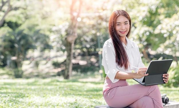 Portret van een mooie aziatische vrouw die buiten zit, glimlacht en naar de camera kijkt terwijl ze op een tabletcomputer werkt.