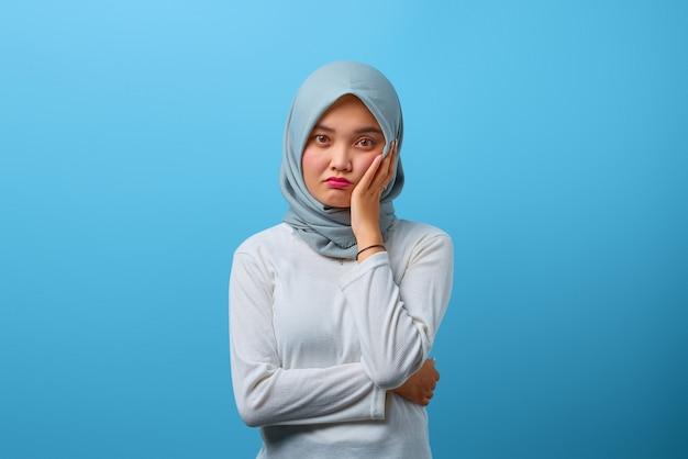 Portret van een mooie aziatische vrouw die er moe en verveeld uitziet met een depressieve uitdrukking