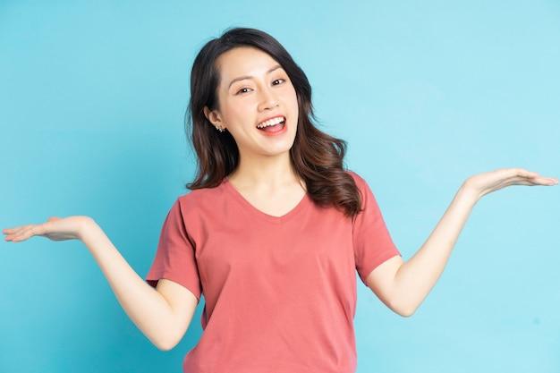 Portret van een mooie aziatische vrouw die haar handen aan haar zij vasthoudt en op een vriendelijke manier glimlacht