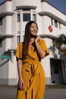Portret van een mooie aziatische vrouw die in de stad poseert terwijl ze een gele jurk draagt