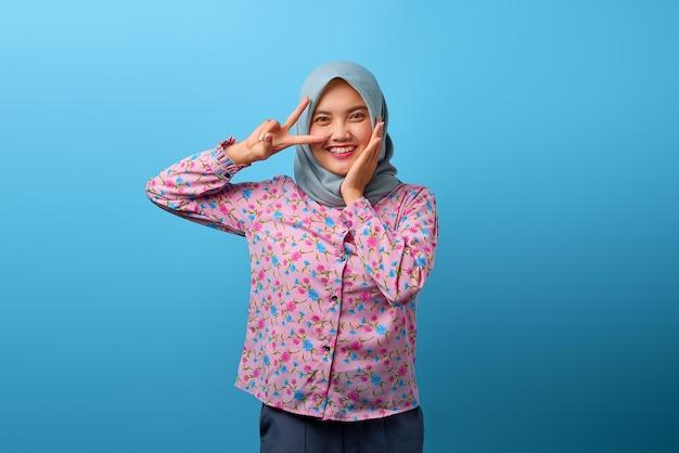 Portret van een mooie aziatische vrouw die lacht en een vredesteken boven het oog toont