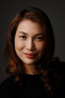 Portret van een mooie aziatische vrouw die lacht en naar de camera kijkt met zelfverzekerde en positieve emotie.