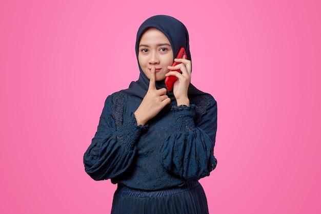 Portret van een mooie aziatische vrouw die met een smartphone praat en vraagt om stil te zijn met een vinger op de lippen