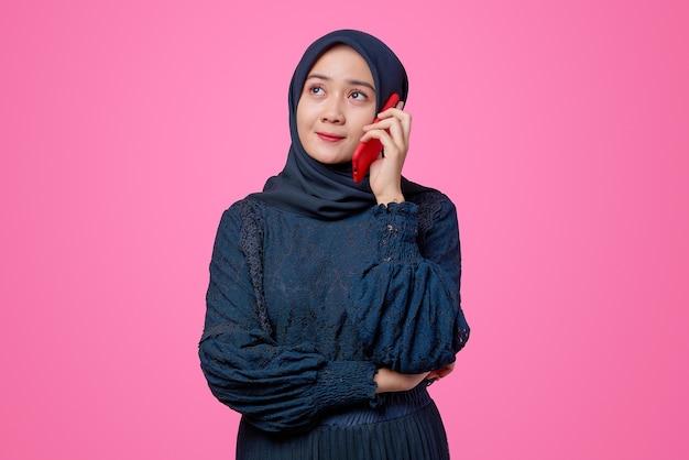 Portret van een mooie aziatische vrouw die met een smartphone praat en wegkijkt