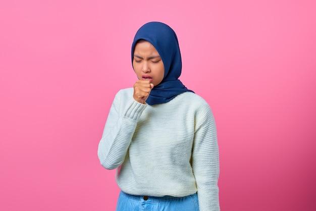 Portret van een mooie aziatische vrouw die zich onwel voelt en hoest op een roze achtergrond