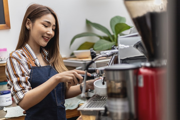 Portret van een mooie aziatische vrouw in een schort met een koffiezetapparaat, ze is eigenaar van een coffeeshop, een concept van een eet- en drankbedrijf. winkelbeheer door een zakenvrouw.