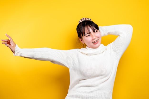 Portret van een mooie aziatische vrouw met een lachend gezicht. aziatische vrouw die vrijetijdskleding draagt. thaise levensstijl. schattige meisjes heldere glimlach op een gele achtergrond