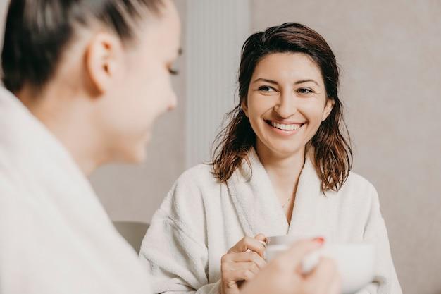 Portret van een mooie blanke brunette lachend tijdens het kijken naar haar vriendin ontspannen na spa-procedures in hun lichaam.