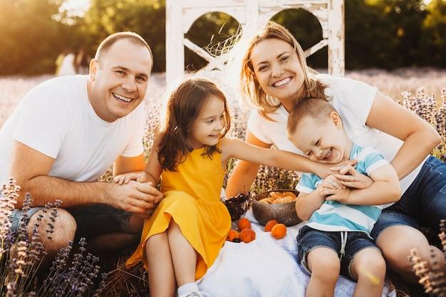 Portret van een mooie blanke familie zittend in een lavendelveld een picknick kijken camera omarmen en lachen en plezier maken tegen zonsondergang.