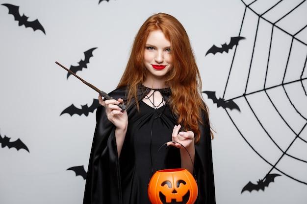 Portret van een mooie blanke heks die oranje pompoen vasthoudt voor het vieren van halloween.