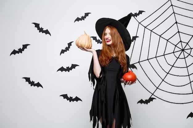 Portret van een mooie blanke heks die pompoen vasthoudt voor het vieren van halloween