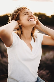 Portret van een mooie blanke vrouw lachend met gesloten ogen met een krans van bloem op haar hoofd tegen zonsondergang.