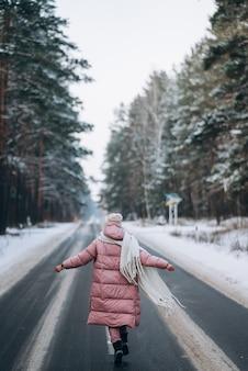 Portret van een mooie blanke vrouw op een weg door besneeuwd bos