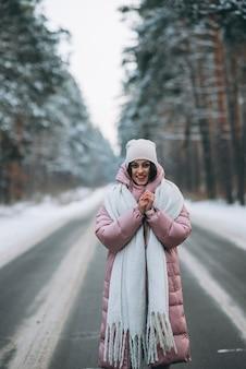 Portret van een mooie blanke vrouw op een weg door besneeuwde bossen
