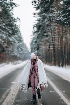Portret van een mooie blanke vrouw op een weg in het besneeuwde bos