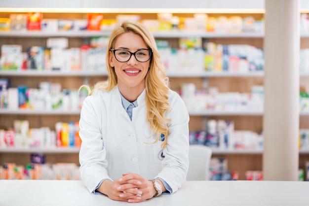 Portret van een mooie blonde apotheker die op teller bij farmaceutische opslag leunt.