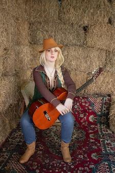 Portret van een mooie blonde cowgirl met een gitaar op de hooizolder