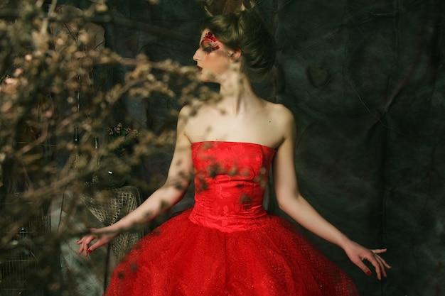 Portret van een mooie blonde vrouw in een rode jurk. creatieve make-up en kapsel. geschoten in een fantasiehuis.