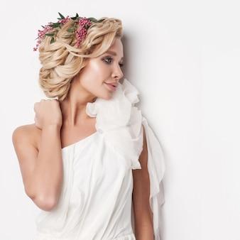 Portret van een mooie blonde vrouw met bloemen in haar haar.