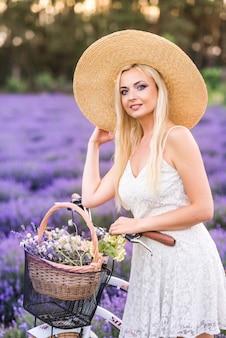 Portret van een mooie blonde vrouw met een fiets in lavendel.