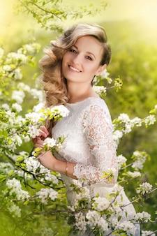 Portret van een mooie blondevrouw in een tot bloei komende tuin