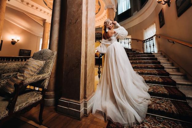 Portret van een mooie bruid die een mooie trap beklimt.