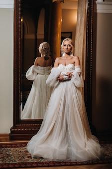 Portret van een mooie bruid die zich met haar terug naar de spiegel bevindt.