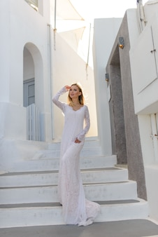 Portret van een mooie bruid in een witte jurk. een meisje poseert op een achtergrond van witte trappen en witte muren in oia, santorini.