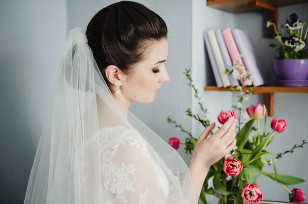 Portret van een mooie bruid. kosten in de ochtend thuis. zwart-wit foto. klassieke bruiloft.