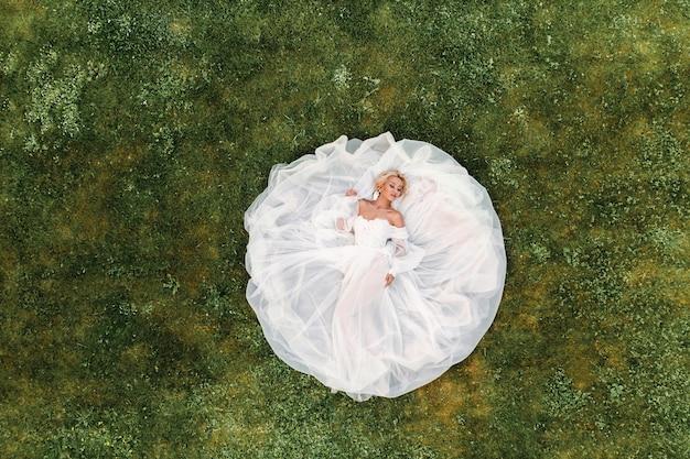 Portret van een mooie bruid liggend op de grond in een witte trouwjurk. foto van een elegante bruid op het groene gras. bovenste foto van de bruid.