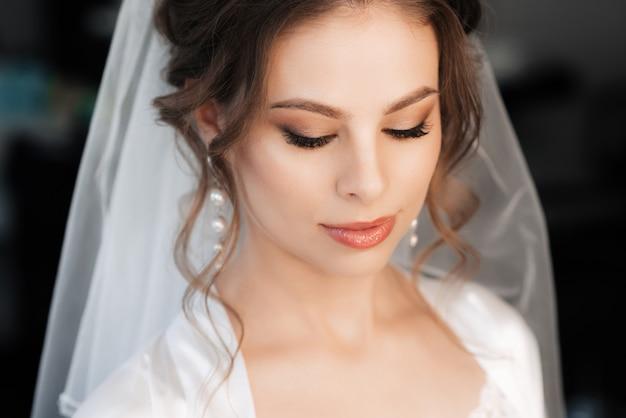 Portret van een mooie bruid met make-up en haar styling