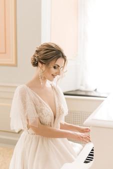 Portret van een mooie bruid naast een piano in een luxe interieur