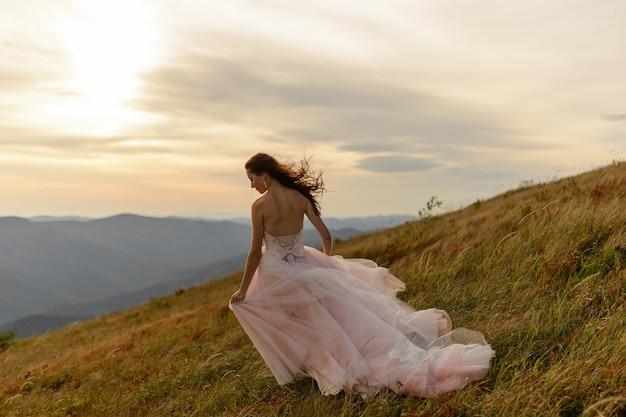 Portret van een mooie bruid op een achtergrond van herfst bergen. een sterke wind blaast haar haar en haar jurk. huwelijksceremonie bovenop de berg. vrije ruimte.