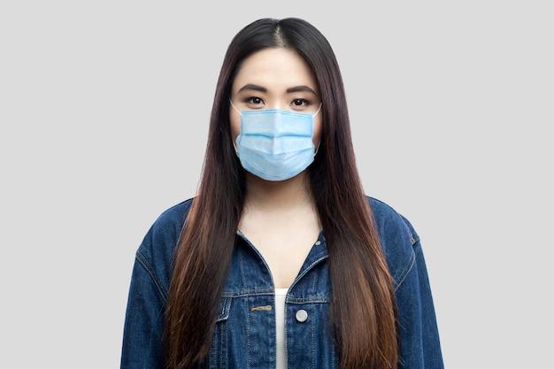 Portret van een mooie brunette aziatische jonge vrouw met een chirurgisch medisch masker in een blauwe spijkerjas die staat en naar de camera kijkt. indoor studio opname, geïsoleerd op lichtgrijze achtergrond.