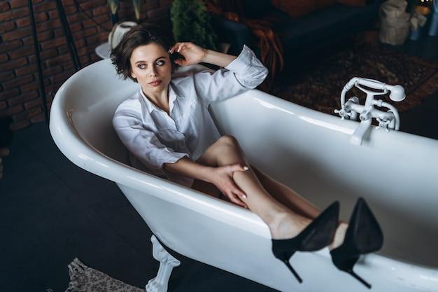 Portret van een mooie brunette die in een lege badkamers ligt die benen omhoog houdt, een wit overhemd en zwarte schoenen draagt