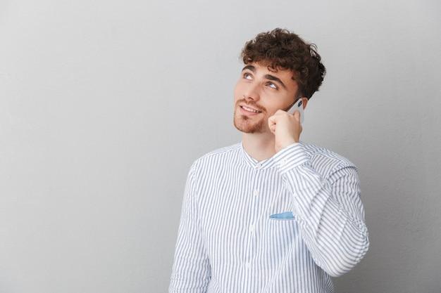 Portret van een mooie brunette man gekleed in een shirt glimlachend terwijl hij een smartphone vasthoudt en praat, geïsoleerd over een grijze muur
