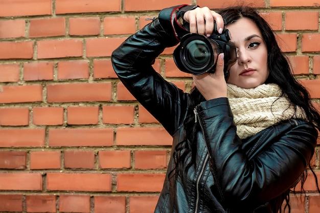 Portret van een mooie brunette meisje fotograaf met lang krullend haar in warme herfst kleding