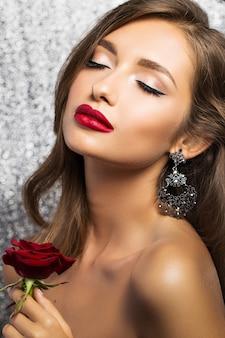Portret van een mooie brunette met een rode roos