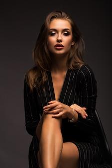 Portret van een mooie brunette op een grijze geïsoleerde achtergrond. luxueus meisje met mooie lippen.
