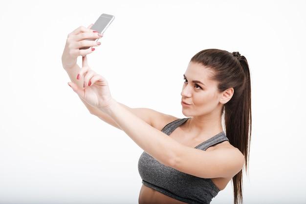 Portret van een mooie brunette sportvrouw die selfie neemt met haar mobiele telefoon geïsoleerd
