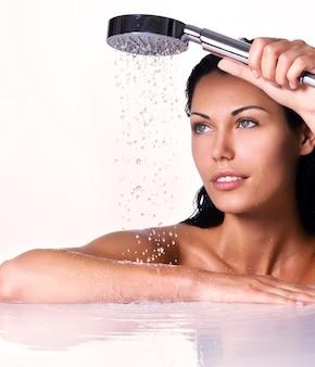 Portret van een mooie brunette vrouw houdt douche in handen met vallend water