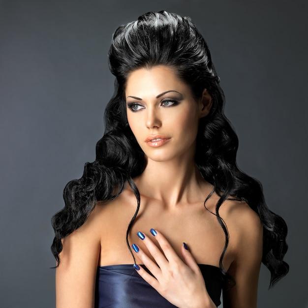 Portret van een mooie brunette vrouw met lang creatief kapsel