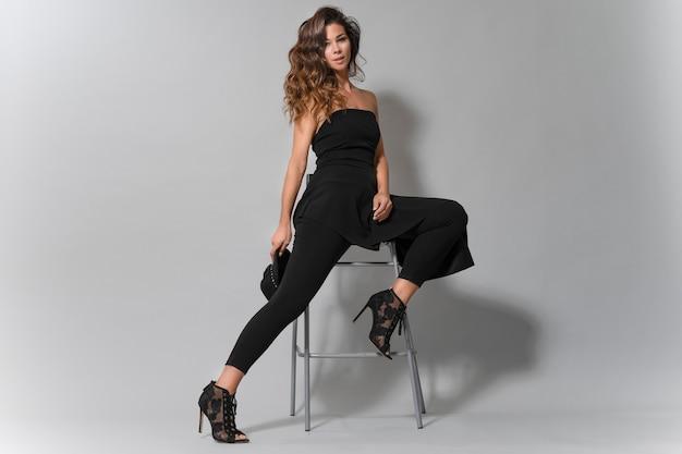 Portret van een mooie brunette vrouw met mooie glimlach, gekleed in zwarte kleding zitten
