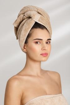 Portret van een mooie chique jonge vrouw na bad of spastanding bedekt met een handdoek.