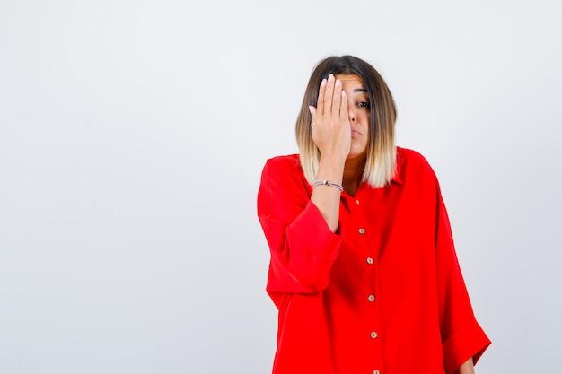 Portret van een mooie dame die de hand op het oog houdt in een rode blouse en een angstig vooraanzicht kijkt