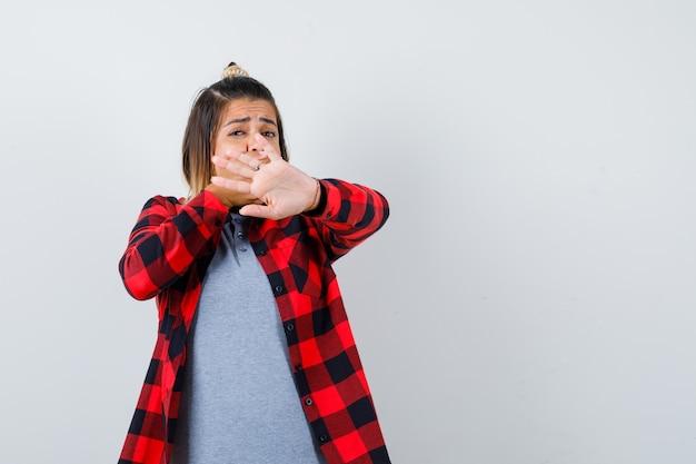 Portret van een mooie dame die een stopgebaar toont, de hand op de mond houdt in vrijetijdskleding en een angstig vooraanzicht kijkt